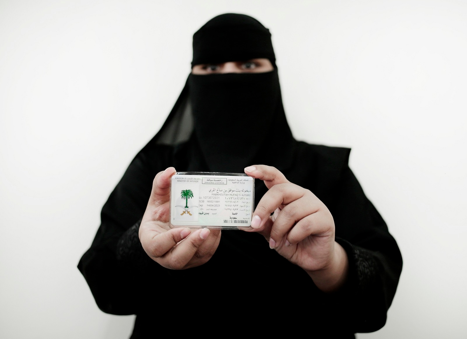 In this June 23, 2018 photo, 27-year old Mabkhoutah al-Mari poses for a photograph holding her new car license at the Saudi Driving School inside Princess Nora University in Saudi Arabia. (AP Photo/Nariman El-Mofty)