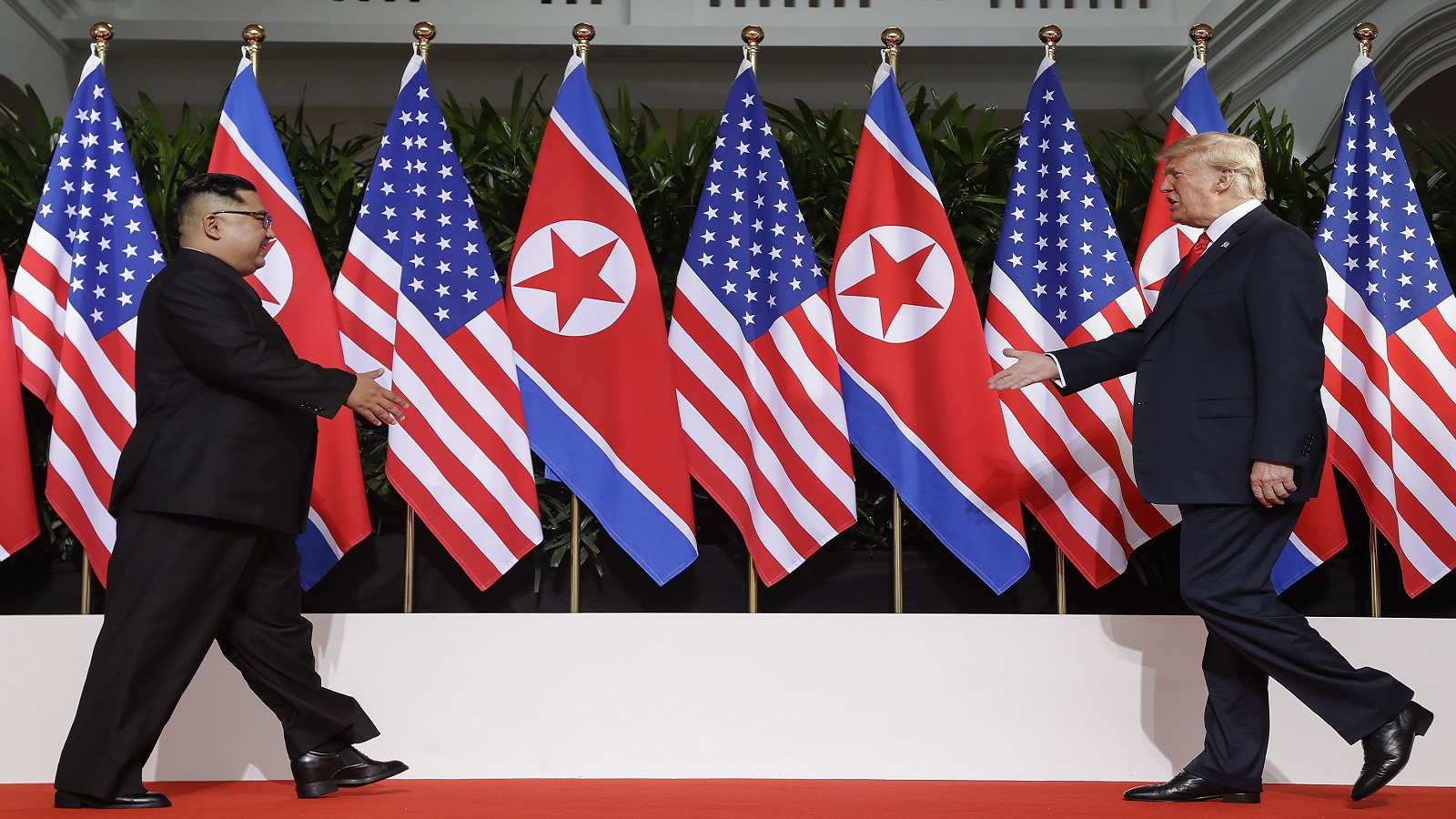 US President Donald Trump and North Korea leader Kim Jong Un walks toward each other at the Capella resort on Sentosa Island Tuesday, June 12, 2018 in Singapore. (AP Photo/Evan Vucci)