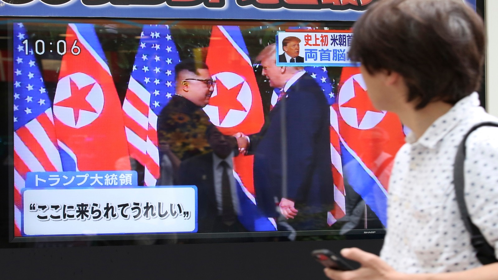 A man looks at a TV screen showing Kim Jong Un, left, and Donald Trump shaking hands before their meeting in Singapore, in Tokyo. Japanese letters read: