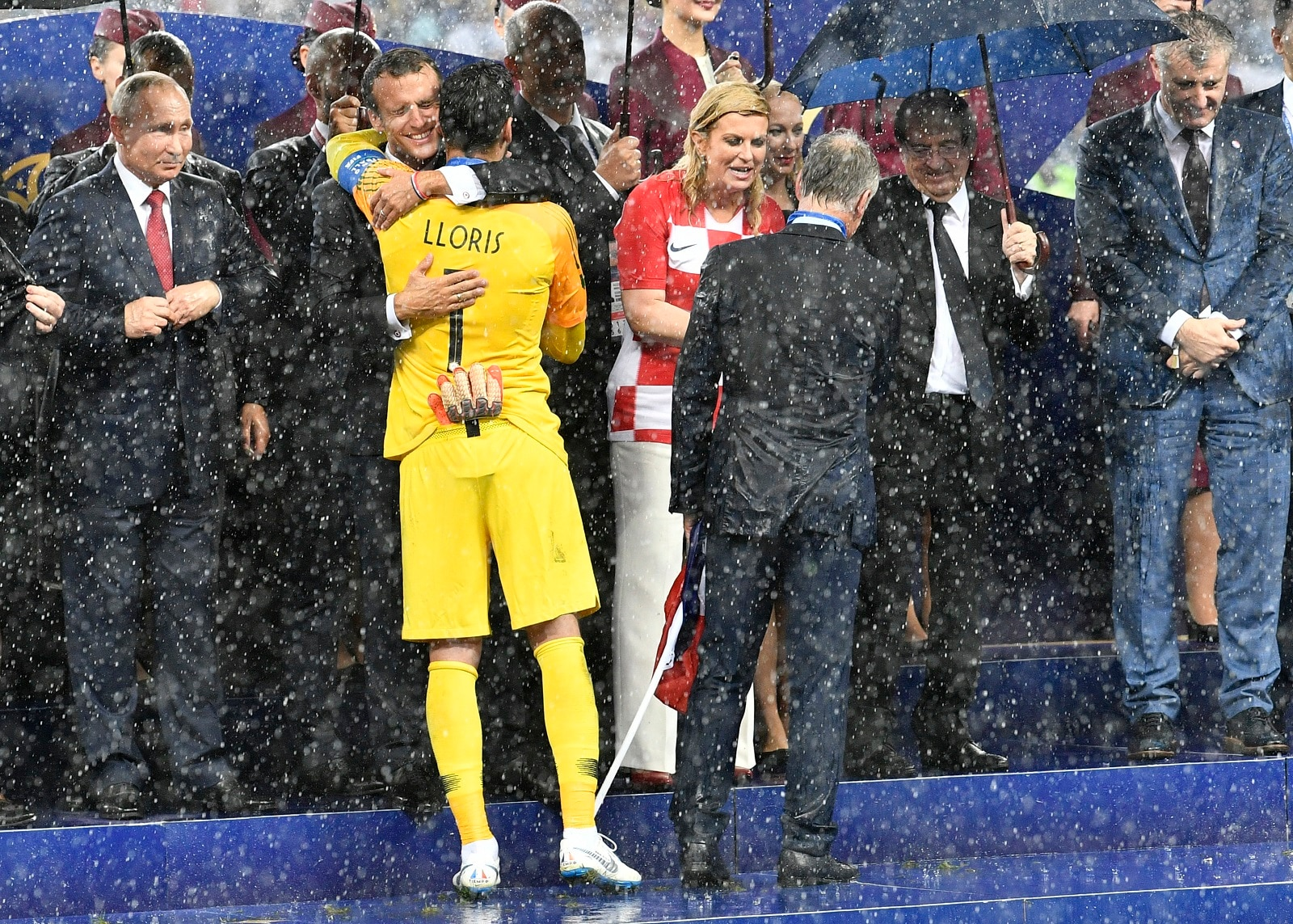 Russian President Vladimir Putin, from left, looks on as French President Emmanuel Macron hugs France goalkeeper Hugo Lloris and Croatian President Kolinda Grabar-Kitarovic congratulates France head coach Didier Deschamps after France won 4-2 in the final match between France and Croatia at the 2018 soccer World Cup in the Luzhniki Stadium in Moscow, Russia, Saturday, July 14, 2018. (AP Photo/Martin Meissner)