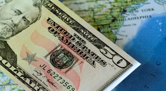 Dollar holds steady as trade tensions keep markets on edge