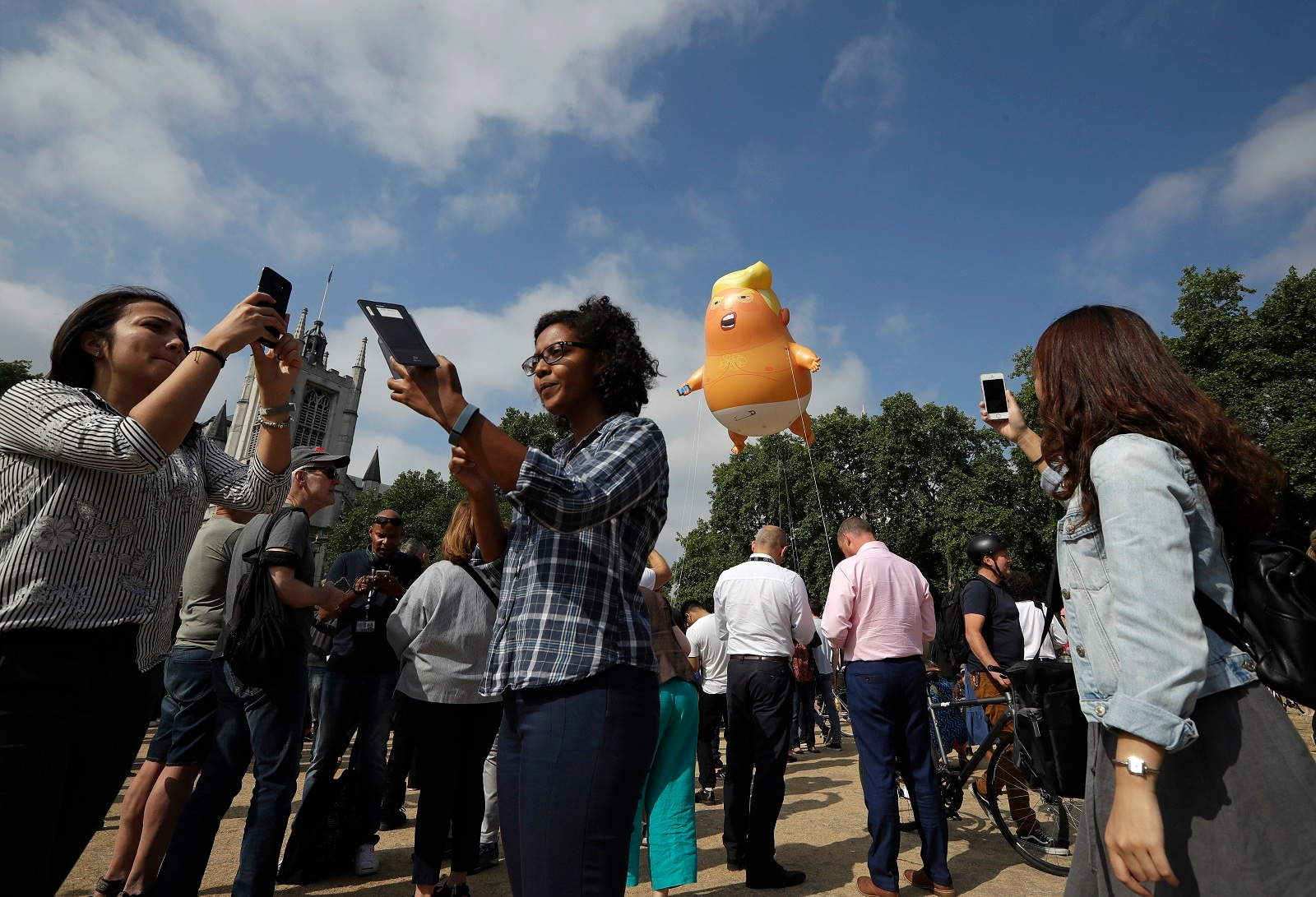 People take photos of a six-meter high cartoon baby blimp of US President Donald Trump is flown as a protest against his visit, in Parliament Square in London, England, on July 13, 2018. (AP Photo/Matt Dunham)
