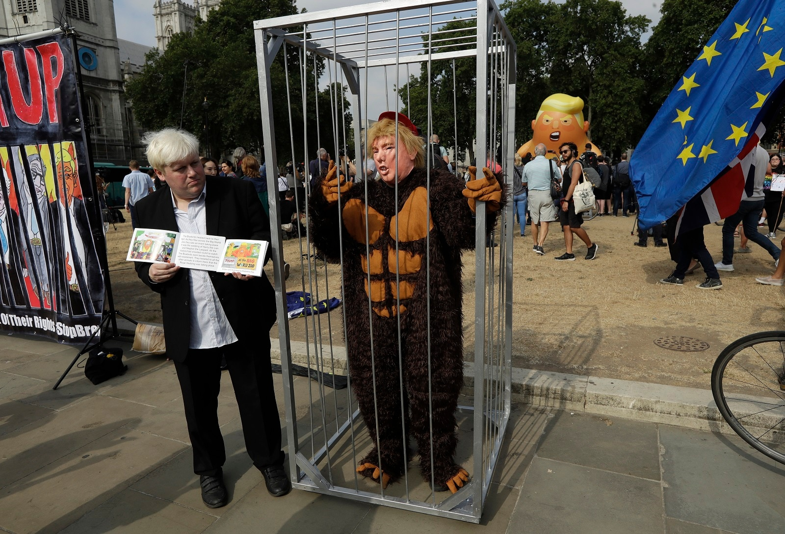A lookalike of former British Foreign Minister Boris Johnson stands next to a person in a cage wearing a money suit and a mask of U.S. President Donald Trump as a six-meter high cartoon baby blimp of Trump is inflated as a protest against his visit, in Parliament Square in London, England, on July 13, 2018. (AP Photo/Matt Dunham)