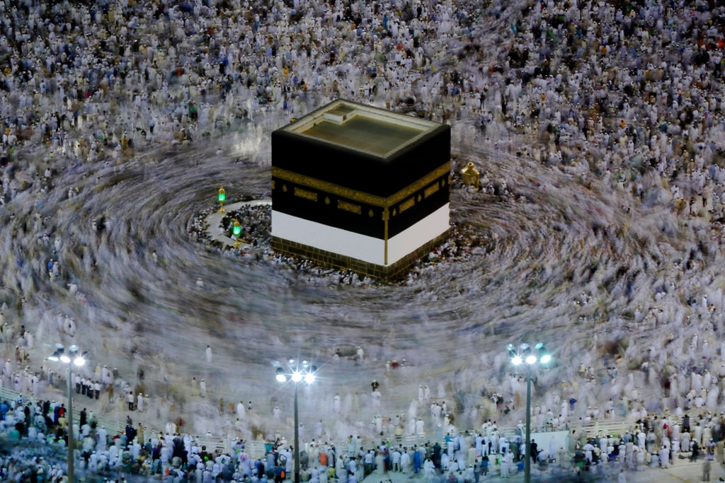 In this Aug. 16, 2018, photo taken with a long exposure, Muslim pilgrims circle the Kaaba as they pray at the Grand Mosque, ahead of the annual Hajj pilgrimage in the Muslim holy city of Mecca, Saudi Arabia. The annual Islamic pilgrimage draws millions of visitors each year, making it the largest yearly gathering of people in the world. (AP Photo/Dar Yasin)