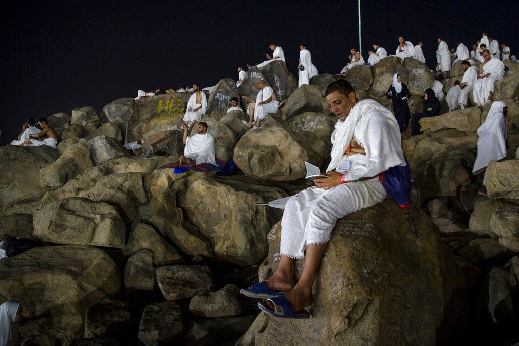 Muslim hajji pilgrims pray at Jabal Al Rahma holy mountain, or the mountain of forgiveness, at Arafat for the annual hajj pilgrimage, outside the holy city of Mecca, Saudi Arabia, Monday, Aug. 20, 2018. More than 2 million Muslims have begun the annual hajj pilgrimage, one of the five pillars of Islam which is required of all able-bodied Muslims once in their lifetime. (AP Photo/Dar Yasin)