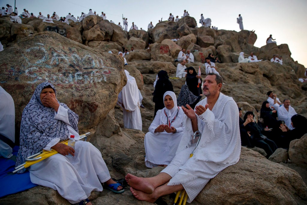 Muslim pilgrims pray at Jabal Al Rahma holy mountain, or the mountain of forgiveness, at Arafat for the annual hajj pilgrimage, outside the holy city of Mecca, Saudi Arabia, Monday, Aug. 20, 2018. More than 2 million Muslims have begun the annual hajj pilgrimage, one of the five pillars of Islam which is required of all able-bodied Muslims once in their lifetime. (AP Photo/Dar Yasin)