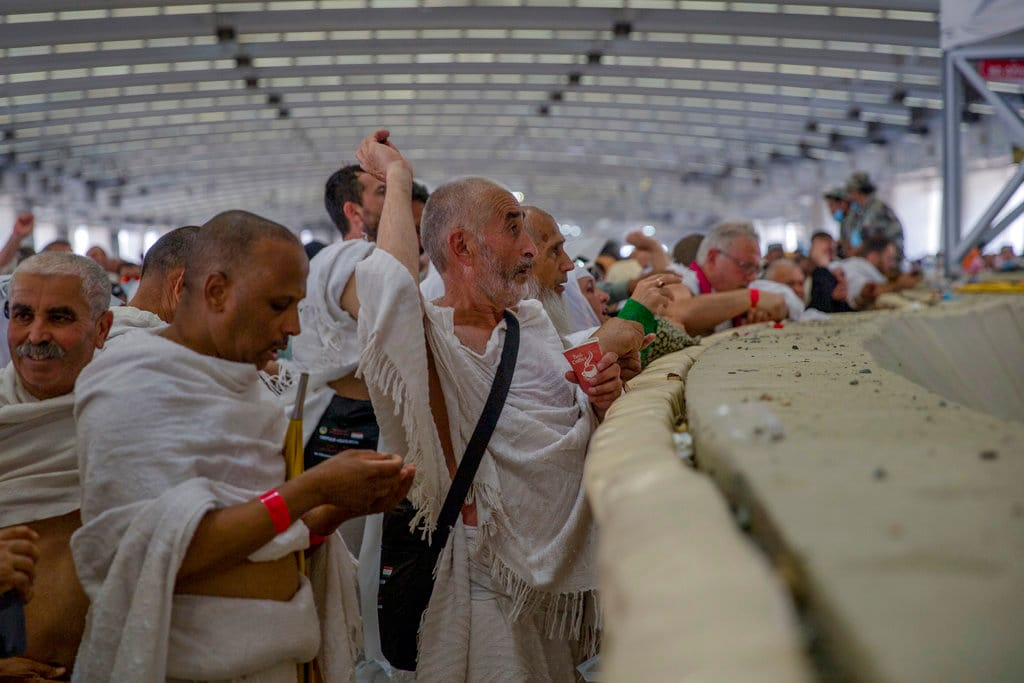Muslim pilgrims cast stones at the huge stone pillar in the symbolic stoning of the devil during the annual Haj pilgrimage on the first day of Eid al-Adha in Mina, outside the holy city of Mecca, Saudi Arabia, Tuesday, Aug. 21, 2018. The five-day pilgrimage represents one of the five pillars of Islam and is required of all able-bodied Muslims once in their life. (AP Photo/Dar Yasin)
