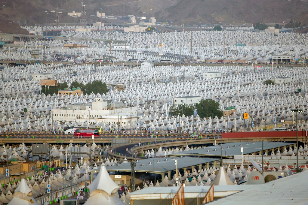 Muslim pilgrims walk back to their tents during the annual Haj pilgrimage on the first day of Eid al-Adha in Mina, outside the holy city of Mecca, Saudi Arabia, Tuesday, Aug. 21, 2018. The five-day pilgrimage represents one of the five pillars of Islam and is required of all able-bodied Muslims once in their life. (AP Photo/Dar Yasin)