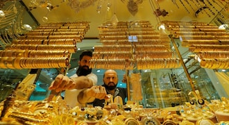 Gold holds losses on rate hike views, trade worries