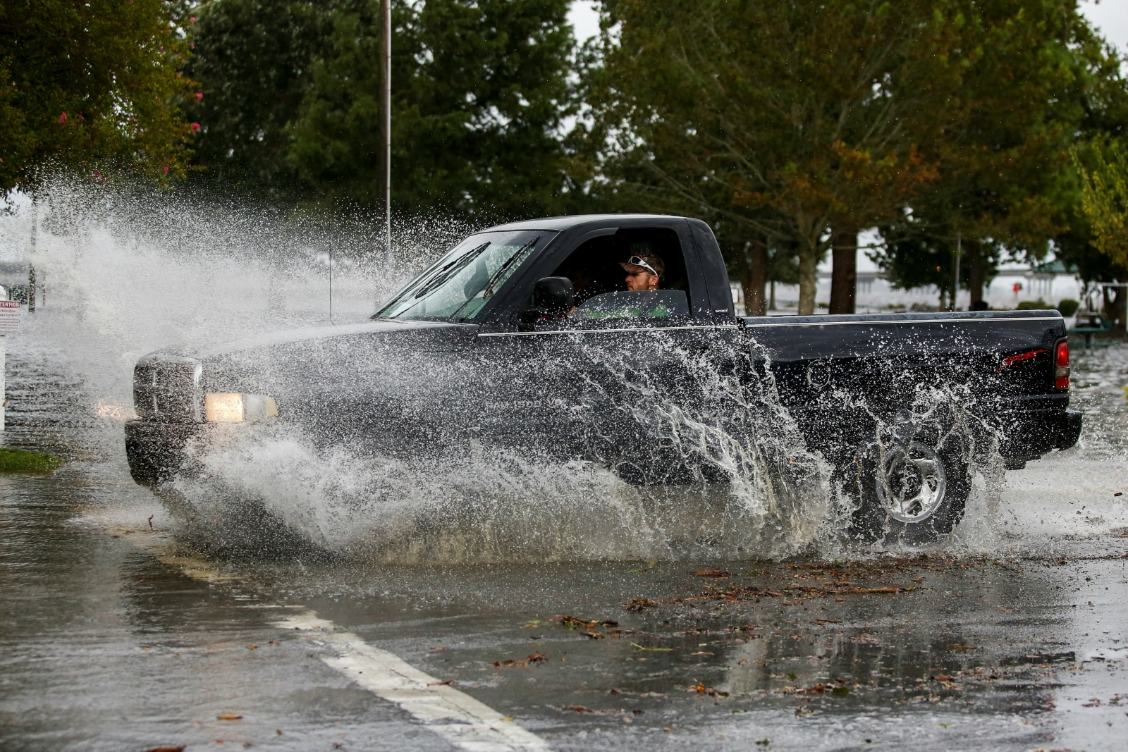 A man drives his car around the flooded Union Point Park Complex as the Hurricane Florence comes ashore in New Bern, North Carolina, US. September 13, 2018. REUTERS/Eduardo Munoz