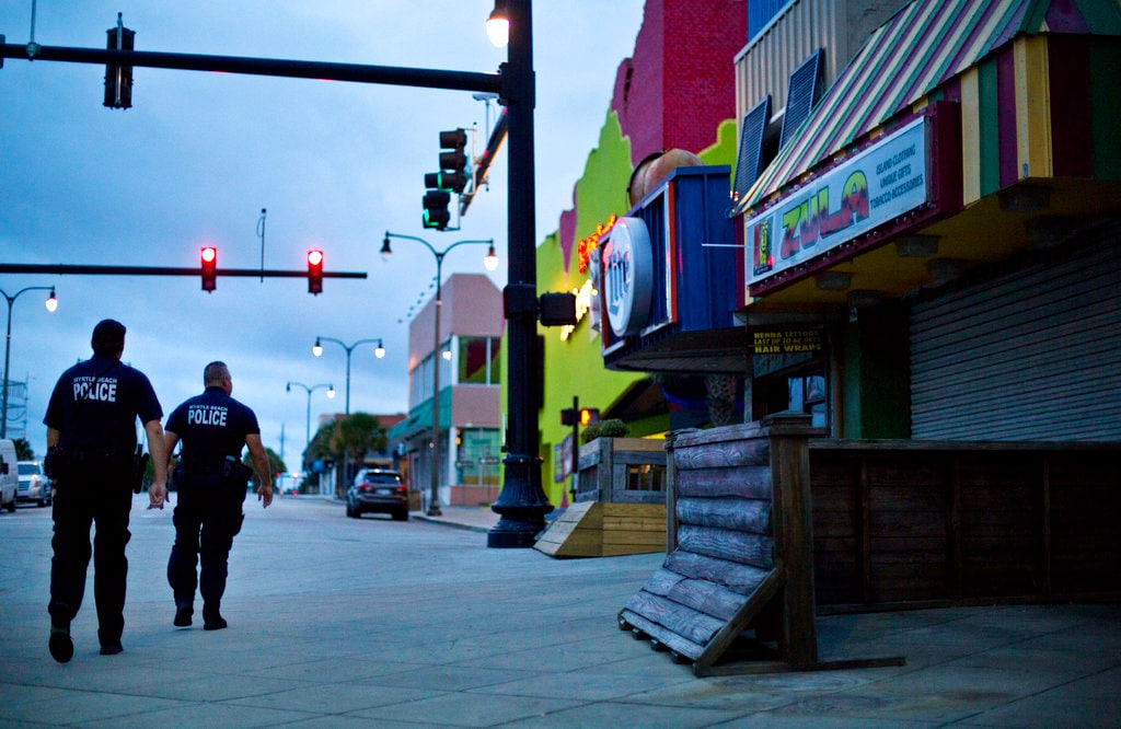 Police patrol past boarded up shops along the boardwalk in Myrtle Beach, S.C., Thursday, Sept. 13, 2018. (AP Photo/David Goldman)