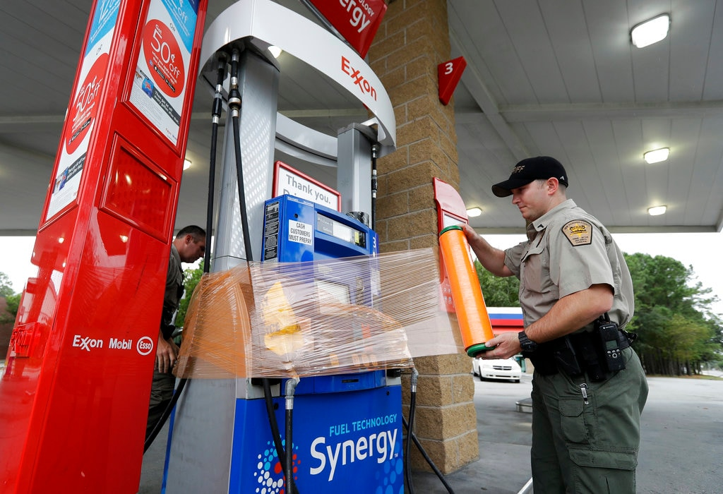 New Hanover Sheriff's Corp. N. Brothers wraps a gas pump for protection in Wilmington, N.C., as Hurricane Florence threatens the coast Thursday, Sept. 13, 2018. (AP Photo/Chuck Burton)