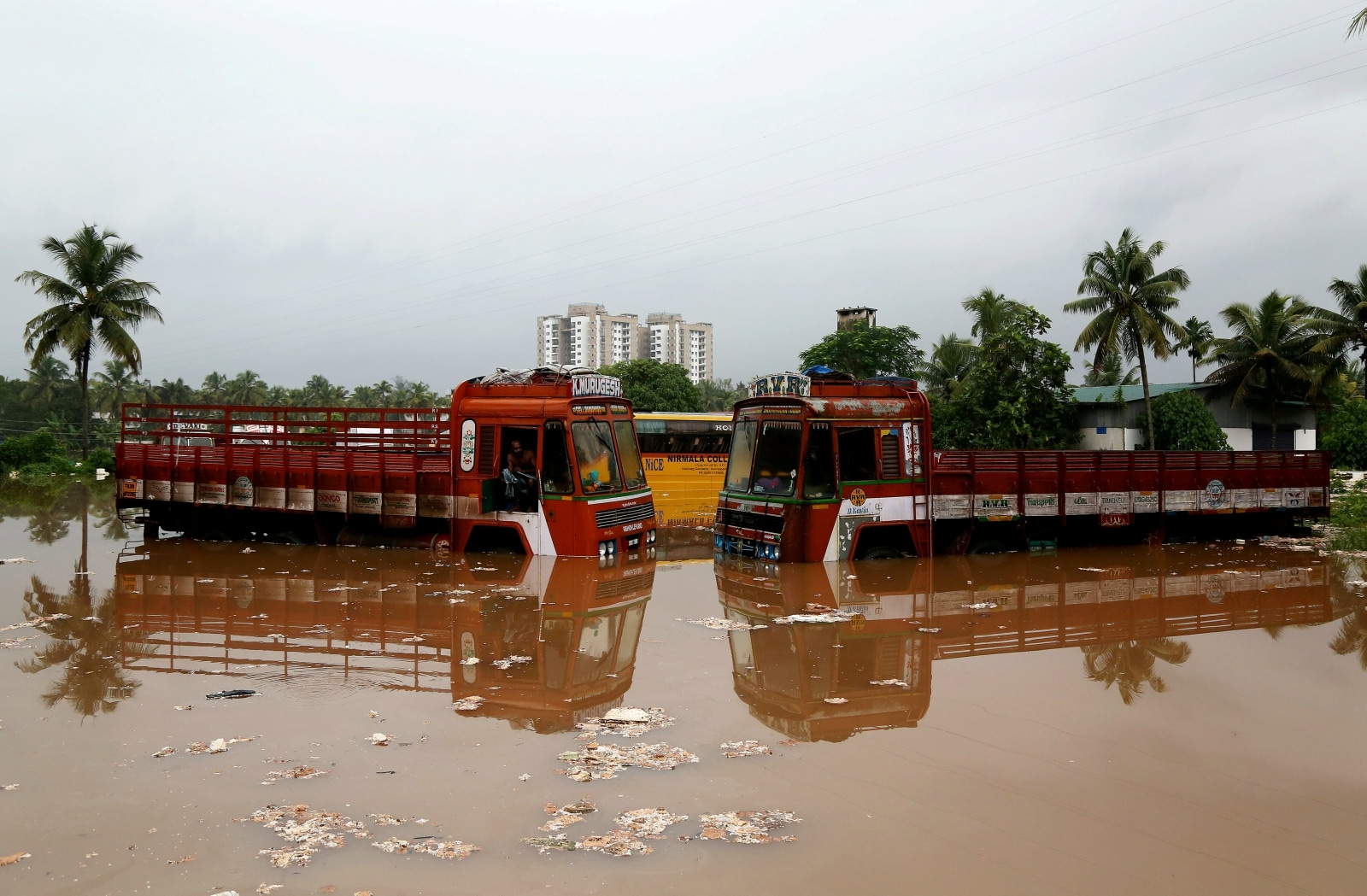 Partially submerged trucks are surrounded by floodwaters at a parking bay after the opening of Idamalayar, Cheruthoni and Mullaperiyar dam gates following heavy rains, on the outskirts of Kochi, Kerala. August 16, 2018. REUTERS/Sivaram V/File Photo