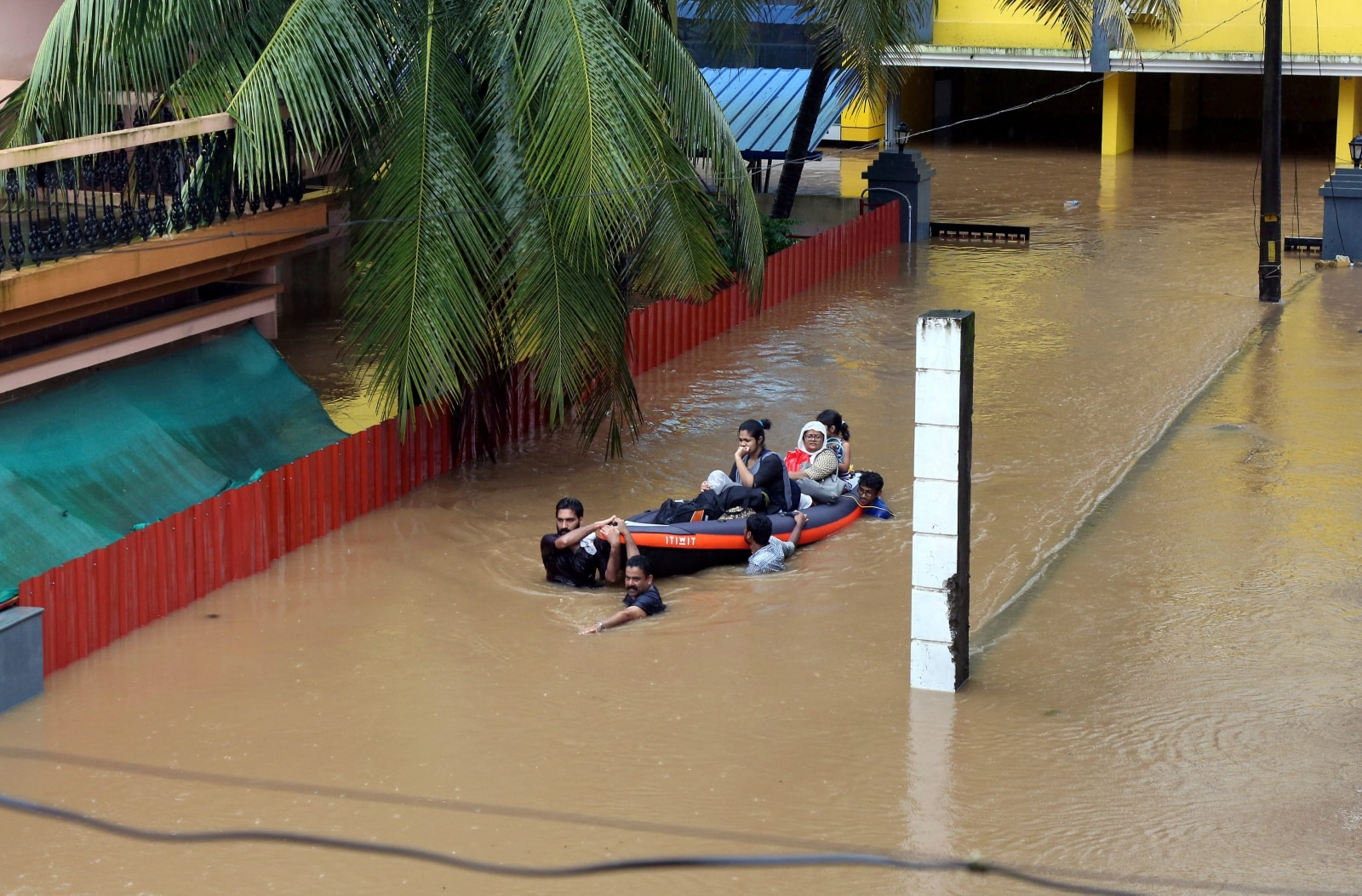 Rescue workers evacuate people from flooded areas after the opening of Idamalayr, Cheruthoni and Mullaperiyar dam gates following heavy rains, on the outskirts of Kochi, India. August 16, 2018. REUTERS/Sivaram V/File Photo