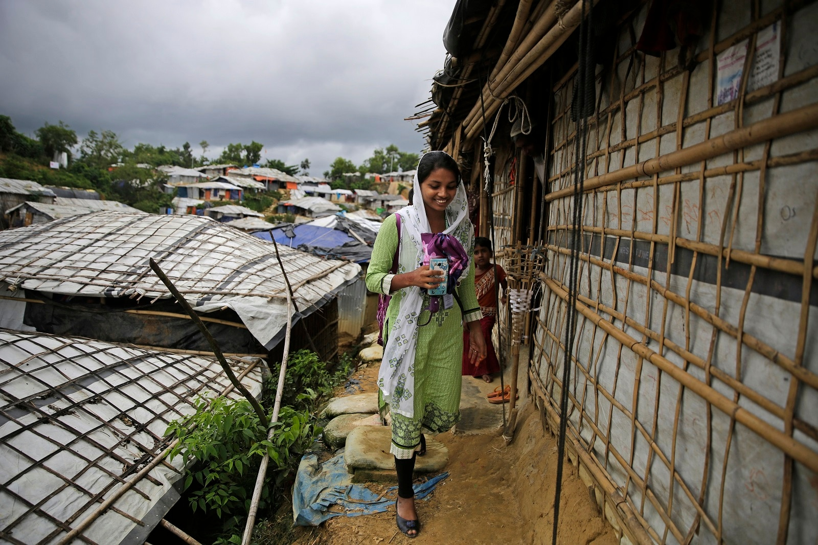 Rahima Akter walks through Balukhali refugee camp in Bangladesh. Rahima is a 19-year-old refugee who dreams of becoming the most educated Rohingya woman in the world. She recently finished high school and hopes to study human rights in college. (AP Photo/Altaf Qadri)