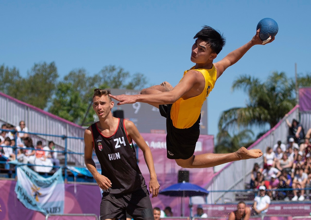 Thailand's Surasak Waenwiset tries a shot as Hungary's Marcell Fenyvesi stands nearby, during their Beach Handball Men's Tournament match in Tecnopolis Park, during the Youth Olympic Summer Games in Buenos Aires, Argentina, Tuesday, Oct. 9, 2018. (Florian Eisele/OIS/IOC via AP)