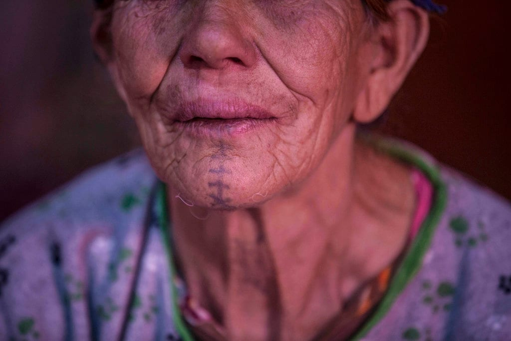 In this Saturday, October 13, 2018 photo, Hadda Oaabjde, 71, poses for a portrait displaying her face tattoo, in the town of Tinguerf, near Azilal, central Morocco. In Morocco's Middle Atlas mountains, an ancient tradition is fading. The distinctive tribal tattoos that indigenous Amazigh women acquired as a rite of passage are slowly disappearing as their aging wearers die. (AP Photo/Mosa'ab Elshamy)