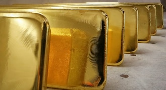 Gold holds near two-week high on dovish central banks