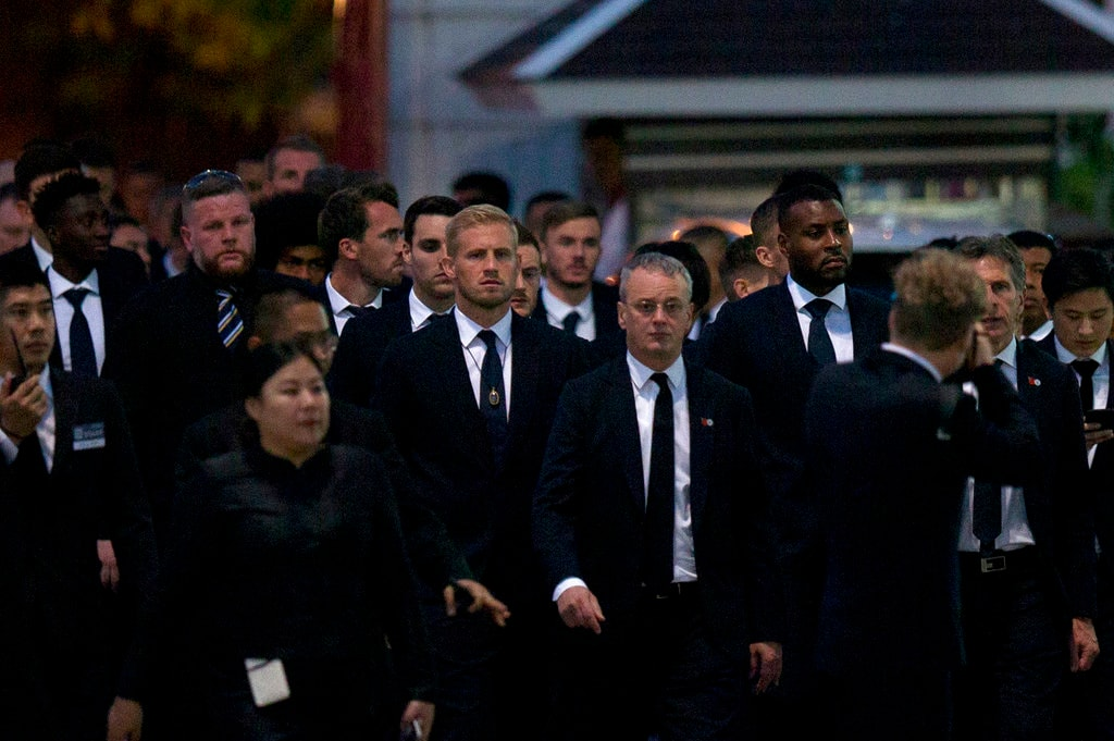 In this Sunday, November 4, 2018, players and officials of the English Premier League club Leicester City arrive at a Buddhist temple to participate in the funeral rituals of Vichai Srivaddhanaprabha in Bangkok, Thailand. An elaborate funeral began Saturday for Thai billionaire and Leicester City owner Vichai Srivaddhanaprabha, who died last week when his helicopter crashed in a parking lot next to the English Premier League club's stadium. (AP Photo/Gemunu Amarasinghe, File)