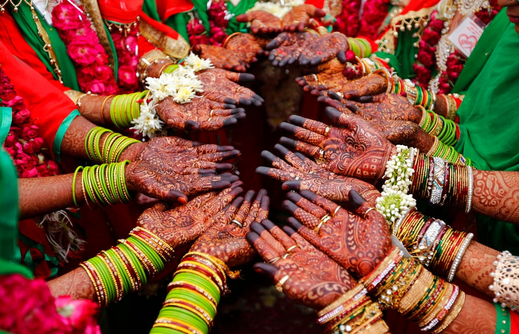 In this Sunday, November 4, 2018, Indian Muslim brides display henna designs on their hands during a mass marriage in Ahmedabad, India. Thirty five couples were married off in a mass marriage ceremony. Mass weddings in India are organized by social organizations primarily to help the economically backward families who cannot afford the high ceremony costs as well as the customary dowry and expensive gifts that are still prevalent in many communities. (AP Photo/Ajit Solanki, File)