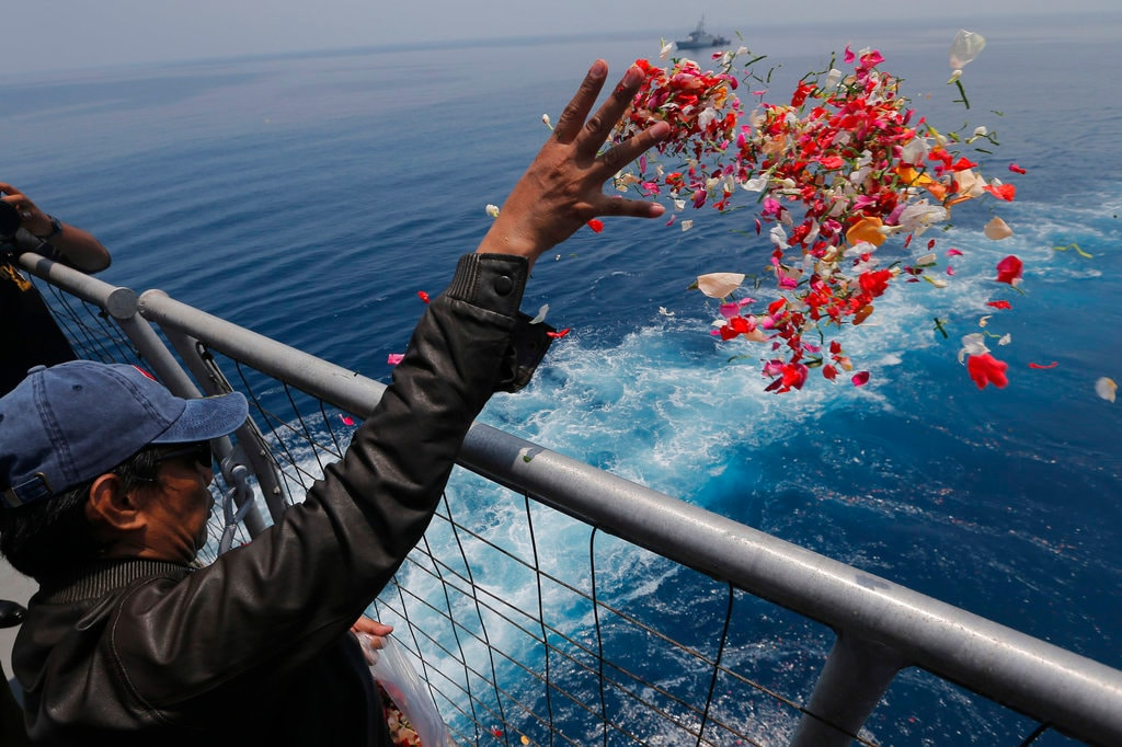 In this Tuesday, November 6, 2018, a relative sprinkles flowers for the victims of the crashed Lion Air flight 610 from an Indonesia Navy ship in the waters where the airplane is believed to have crashed in Tanjung Karawang, Indonesia. (AP Photo/Tatan Syuflana, File)