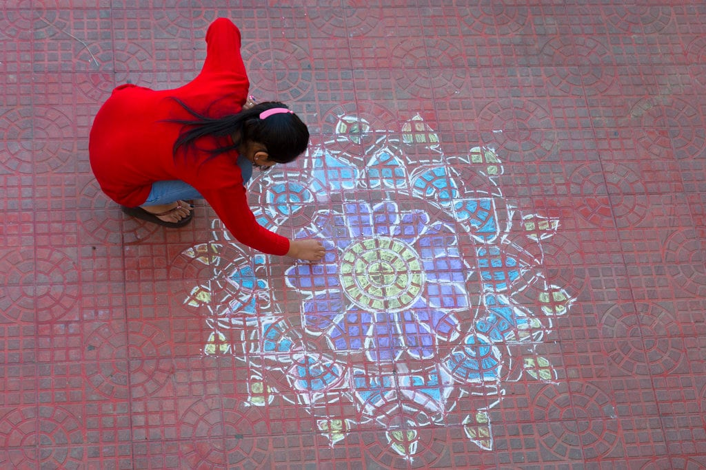 A girl makes a design called 'Rangoli', traditionally made on Diwali, with colored chalk in the courtyard of a house in Dharmsala, India, Wednesday, November 7, 2018. Diwali, the festival of lights was celebrated in most parts of India on Wednesday. (AP Photo/Ashwini Bhatia)