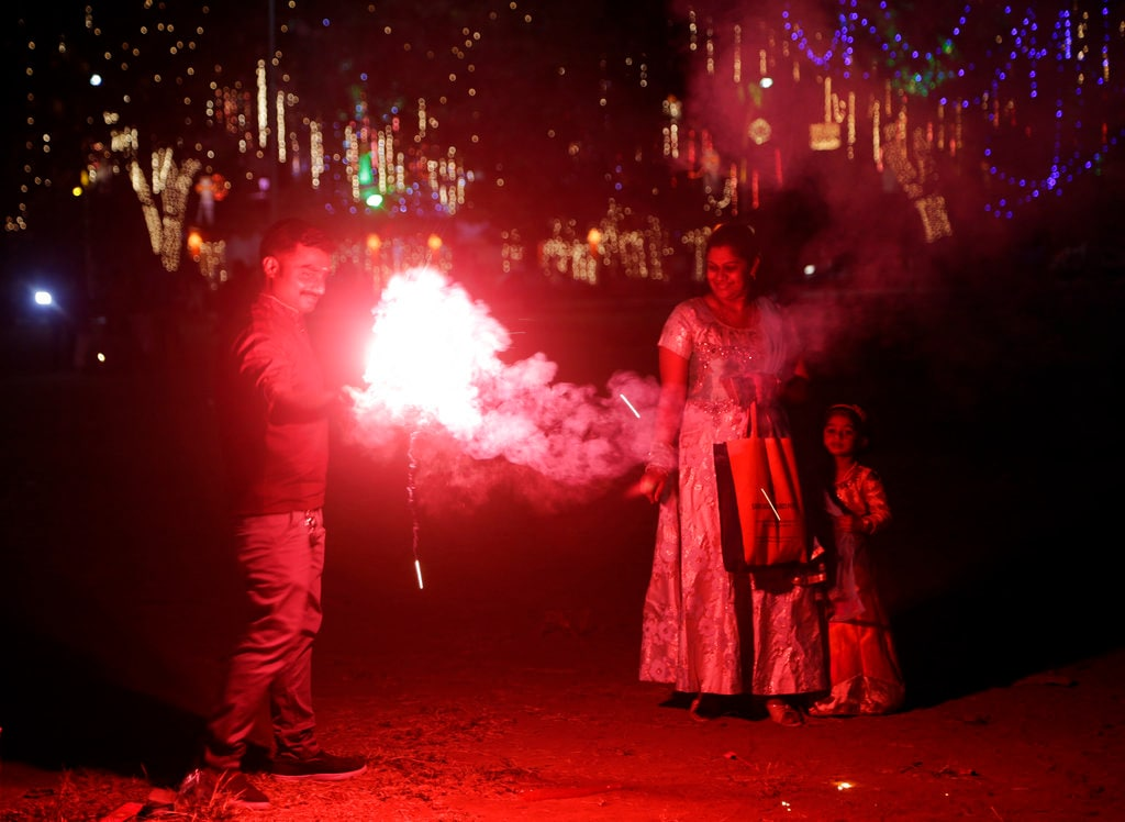 A family lights fire crackers as they celebrate Diwali, the festival of lights at a playground in Mumbai, India, Wednesday, November 7, 2018. (AP Photo/Rajanish Kakade)