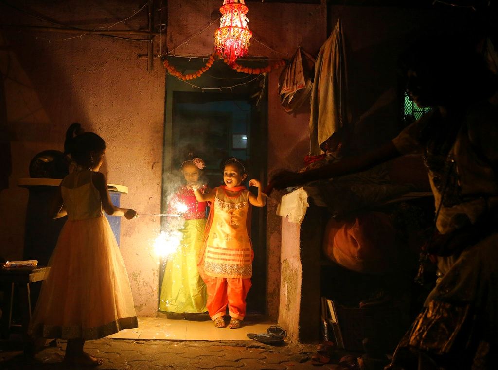 Little girls dressed in traditional attires light fire crackers as they celebrate Diwali, the festival of lights in Mumbai, India, Wednesday, November 7, 2018. (AP Photo/Rafiq Maqbool)