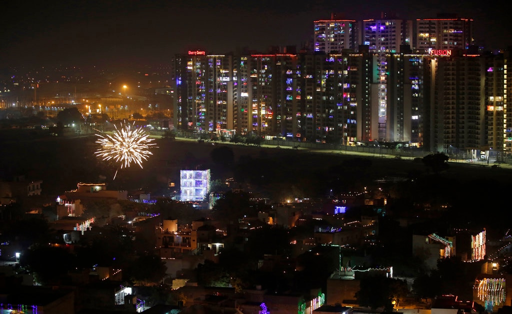A firecracker lights up in the sky, while residential buildings are decorated with colorful lights, during Diwali festival on the outskirts of New Delhi, India, Wednesday, November 7, 2018. (AP Photo/Altaf Qadri)