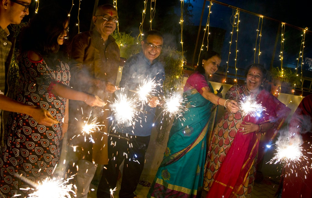 Families gather together to play with firecrackers to traditionally celebrate Diwali in Allahabad, India, Wednesday, November 7, 2018. Diwali, the festival of lights, is one of Hinduism's most important festivals dedicated to the worship of Lakshmi, the Hindu goddess of wealth. (AP Photo/Rajesh Kumar Singh)