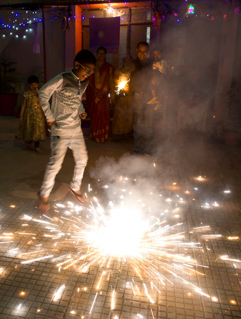 A kid plays with firecrackers to celebrate Diwali in Allahabad, India, Wednesday, November 7, 2018. (AP Photo/Rajesh Kumar Singh)