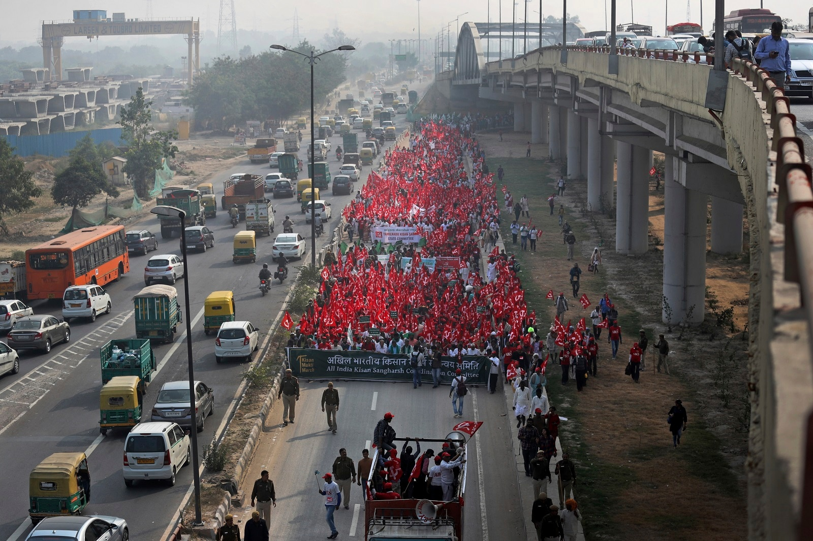 Farmers, workers and agricultural laborers wave red communist flags as they arrive for a two day's protest in New Delhi, India, Thursday, November 29, 2018. (AP Photo/Manish Swarup)