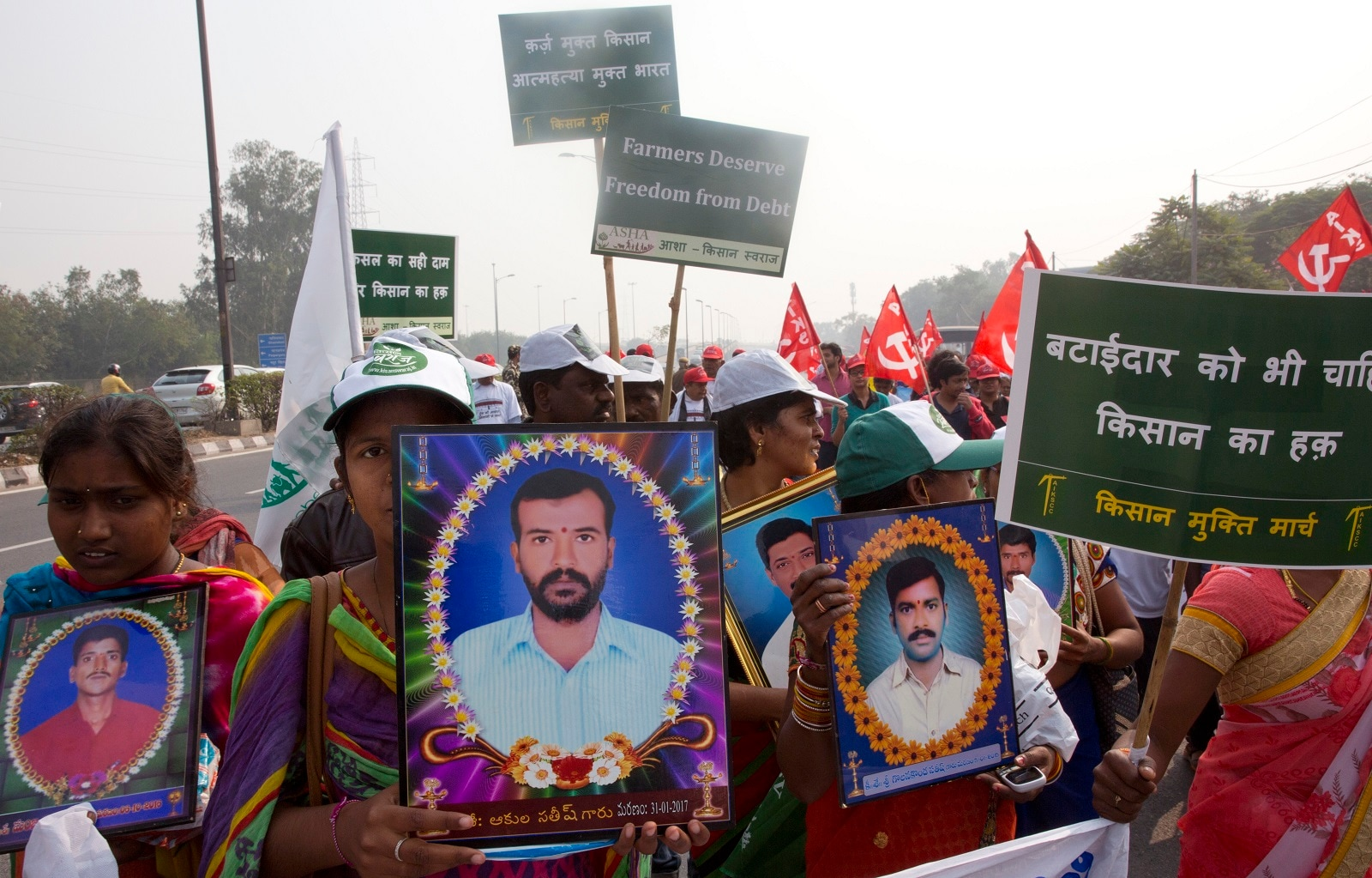 Family members of farmers carry photographs of their relatives who committed suicide as they arrive for a two day's protest in New Delhi, India, Thursday, November 29, 2018. Failed harvests force poor farmers to borrow money at high interest rates to buy seeds, fertilizers and food for their cattle. They often mortgage their land and, as debts mount, some are driven to suicide. Placard on right reads,