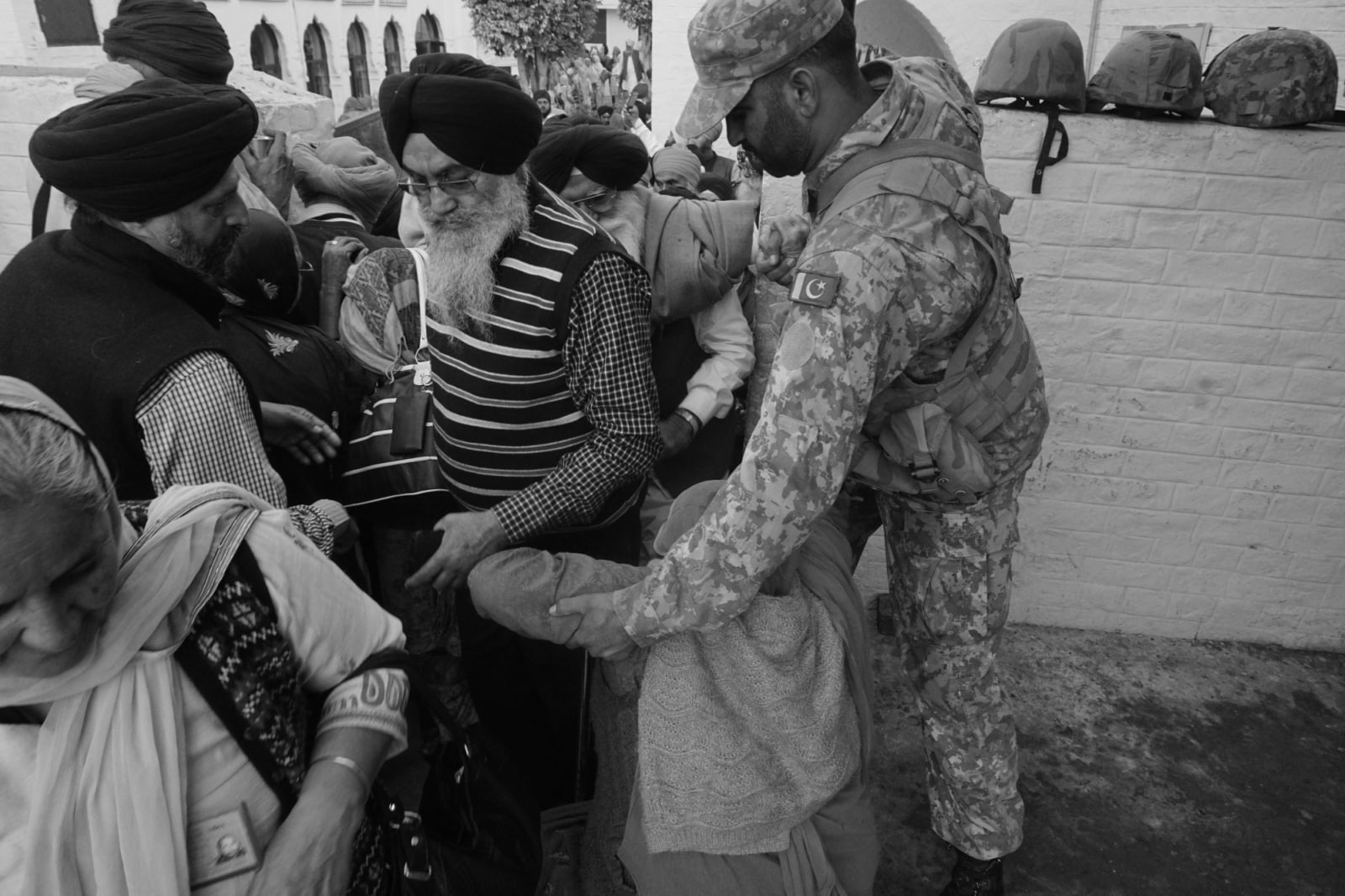 A Pakistan army officer from Punjab regiment helps a Sikh woman at the crowded doorway of the shrine.