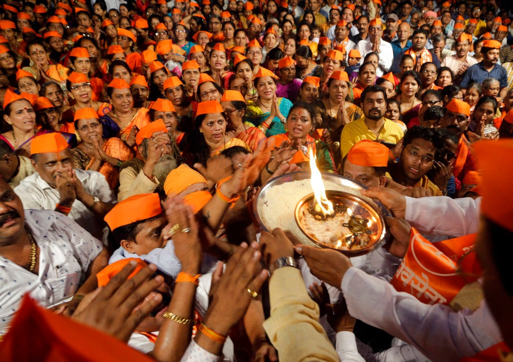 Activists of Hindu nationalist Shiv Sena party perform rituals and offer prayers during a gathering organised to demand the Ram temple be built at Ayodhya, in Mumbai, India, Saturday, November 24, 2018. On December 6, 1992, tens of thousands of Hindu extremists ripped apart the 16th century Babri mosque at Ayodhya in as security forces watched. Hindus say it is the birthplace of their god Ram and contend a temple to him stood on the site before the mosque. (AP Photo/Rajanish Kakade)