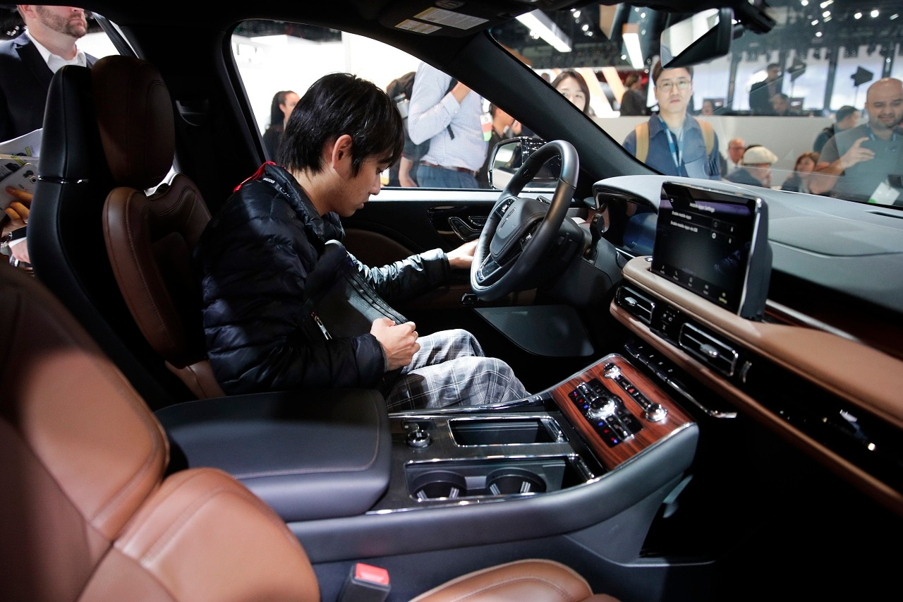 An attendee sits in the 2020 Lincoln Aviator at the Los Angeles Auto Show Wednesday, Nov. 28, 2018, in Los Angeles. (AP Photo/Jae C. Hong)