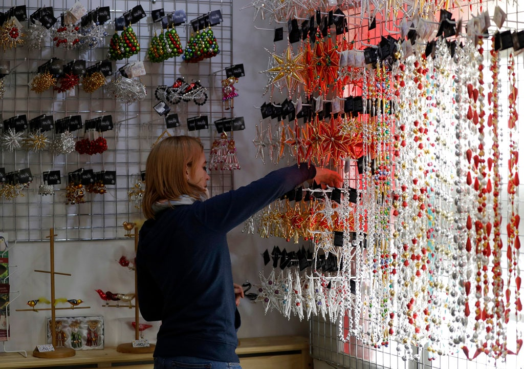 A worker adjusts the shop display of traditional blown glass Christmas decorations in the village of Ponikla, Czech Republic. Wednesday, November 28, 2018. (AP Photo/Petr David Josek)