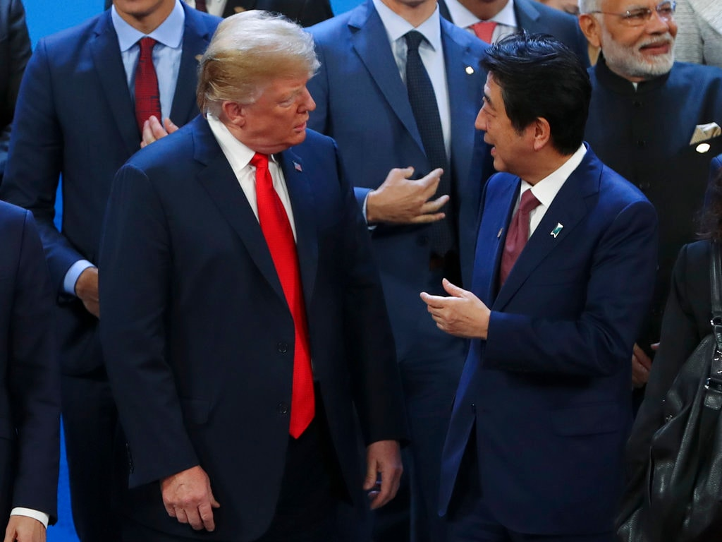 US President Donald Trump, left, listens to Japan's Prime Minister Shinzo Abe as they wait for the family photo of the G20 Leader's Summit at the Costa Salguero Center in Buenos Aires, Argentina, Friday, November 30, 2018. (AP Photo/Ricardo Mazalan)
