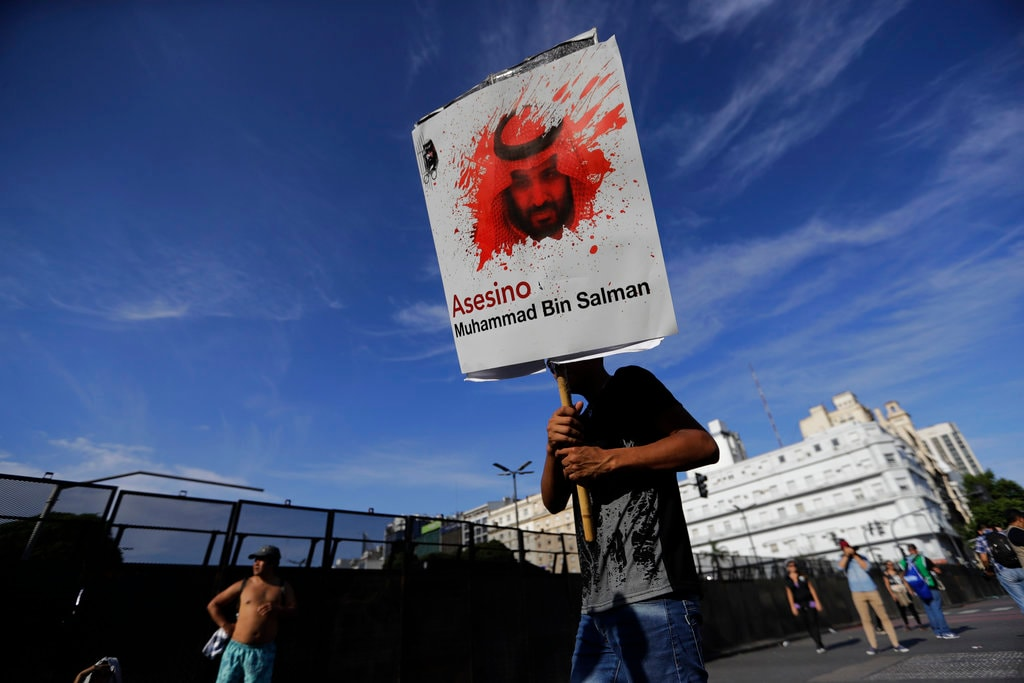 A protester carries a poster with the face of Saudi Arabia's Crown Prince Mohammed bin Salman reading in Spanish