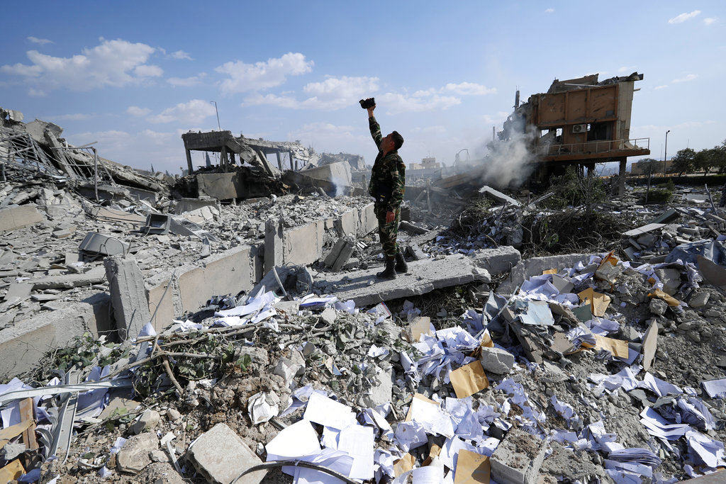 A Syrian soldier films the wreckage of the Syrian Scientific Research Center, which was attacked by US, British and French military strikes to punish President Bashar Assad for a suspected chemical attack against civilians, in the Damascus suburb of Barzeh, Syria, on April 14, 2018. (AP Photo/Hassan Ammar)