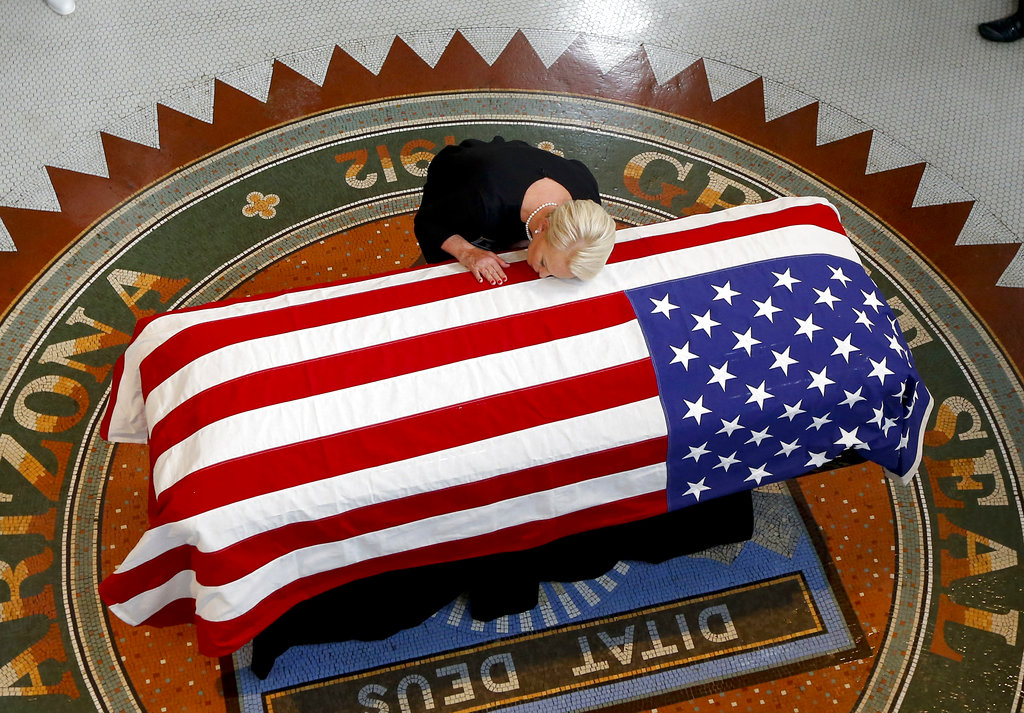 Cindy McCain, wife of Senator John McCain, R-Ariz., rests her head on his casket during a memorial service at the Arizona Capitol in Phoenix on August 29, 2018. (AP Photo/Ross D. Franklin)