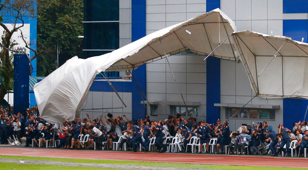Philippine National Police officers and employees react as their tent is toppled by the downwash of a hovering police helicopter performing a salute during the 117th Philippine National Police Service anniversary at Camp Crame in Quezon City, a suburb of Manila, on August 8, 2018. (AP Photo/Bullit Marquez)