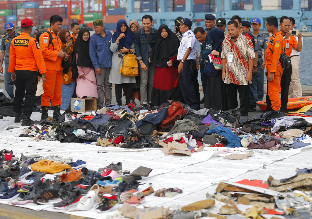Relatives of passengers on the crashed Lion Air jet check personal belongings retrieved from the waters where the airplane is believed to have crashed, at Tanjung Priok Port in Jakarta, Indonesia, on October 31, 2018. (AP Photo/Tatan Syuflana)
