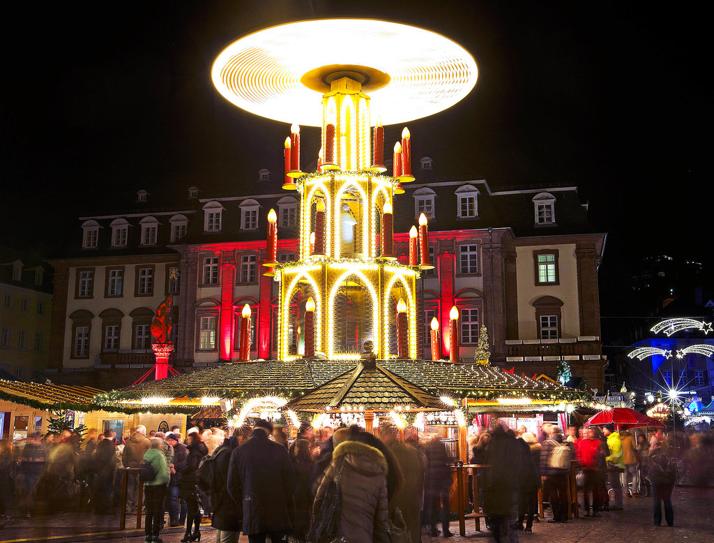 People pay a visit to the traditional Christmas market with a turning pyramid in Heidelberg, Germany.Tuesday, December 4, 2018. (AP Photo/Michael Probst)