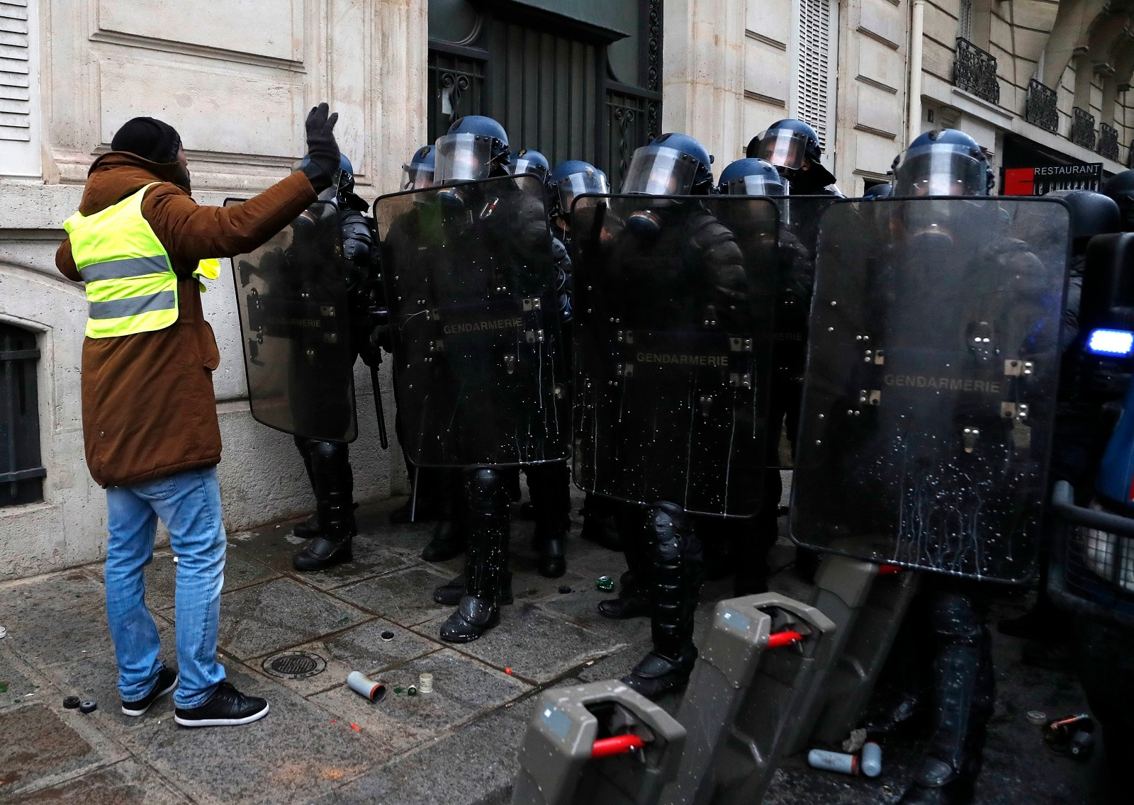 Police officers block a demonstrator wearing yellow vests. (AP Photo/Thibault Camus)