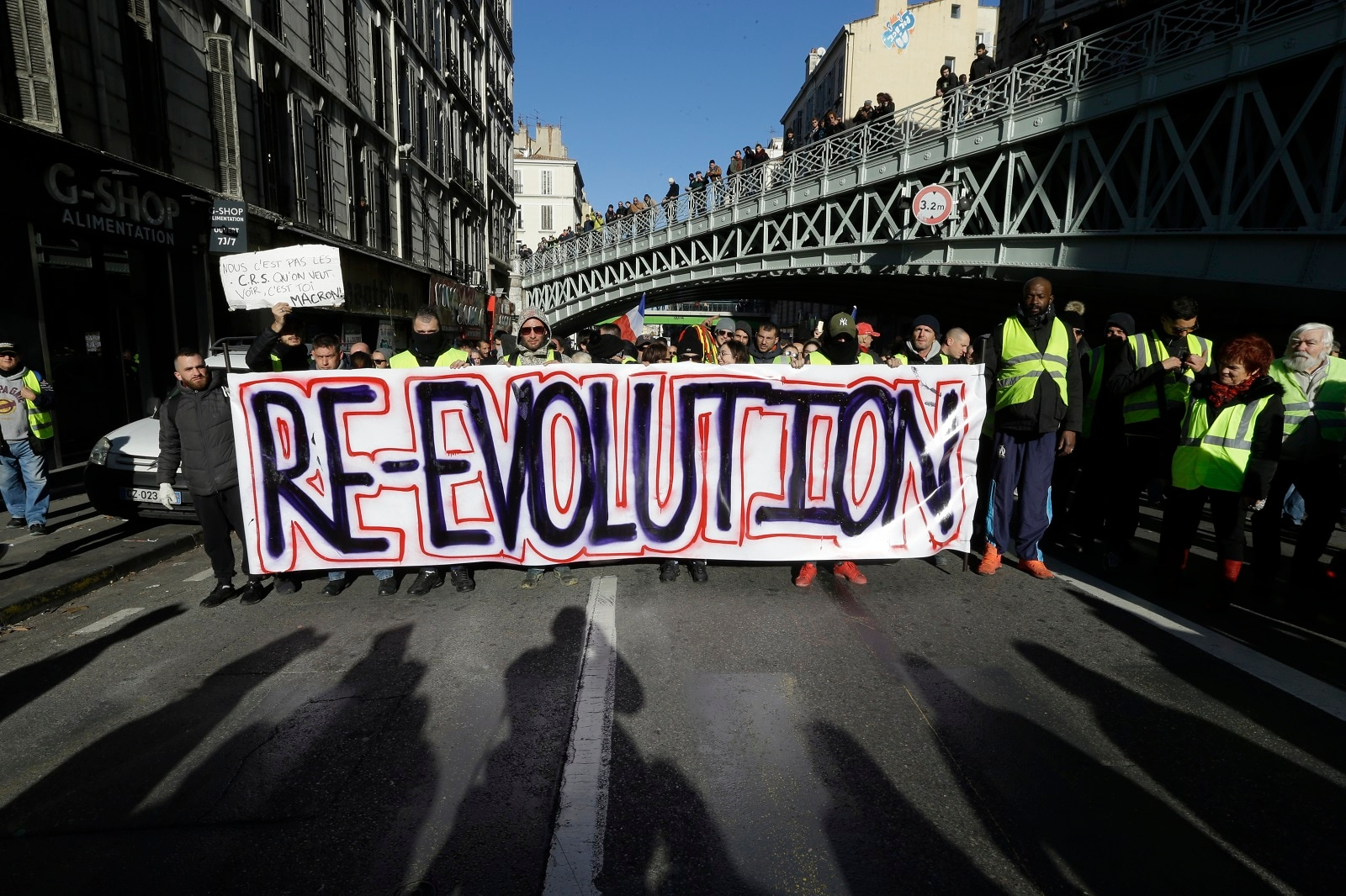 Demonstrators wearing yellow vests hold a banner during a march.(AP Photo/Claude Paris)