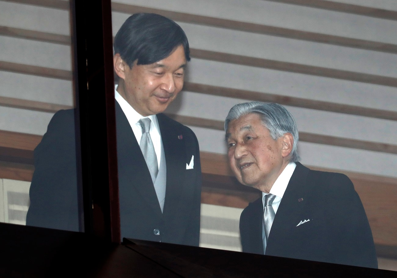 Japan's Emperor Akihito, right, accompanied by Crown Prince Naruhito, left, walks away after greeting well-wishers as they appear on the balcony of the Imperial Palace to mark the emperor's 85th birthday in Tokyo. (AP Photo/Eugene Hoshiko, File)