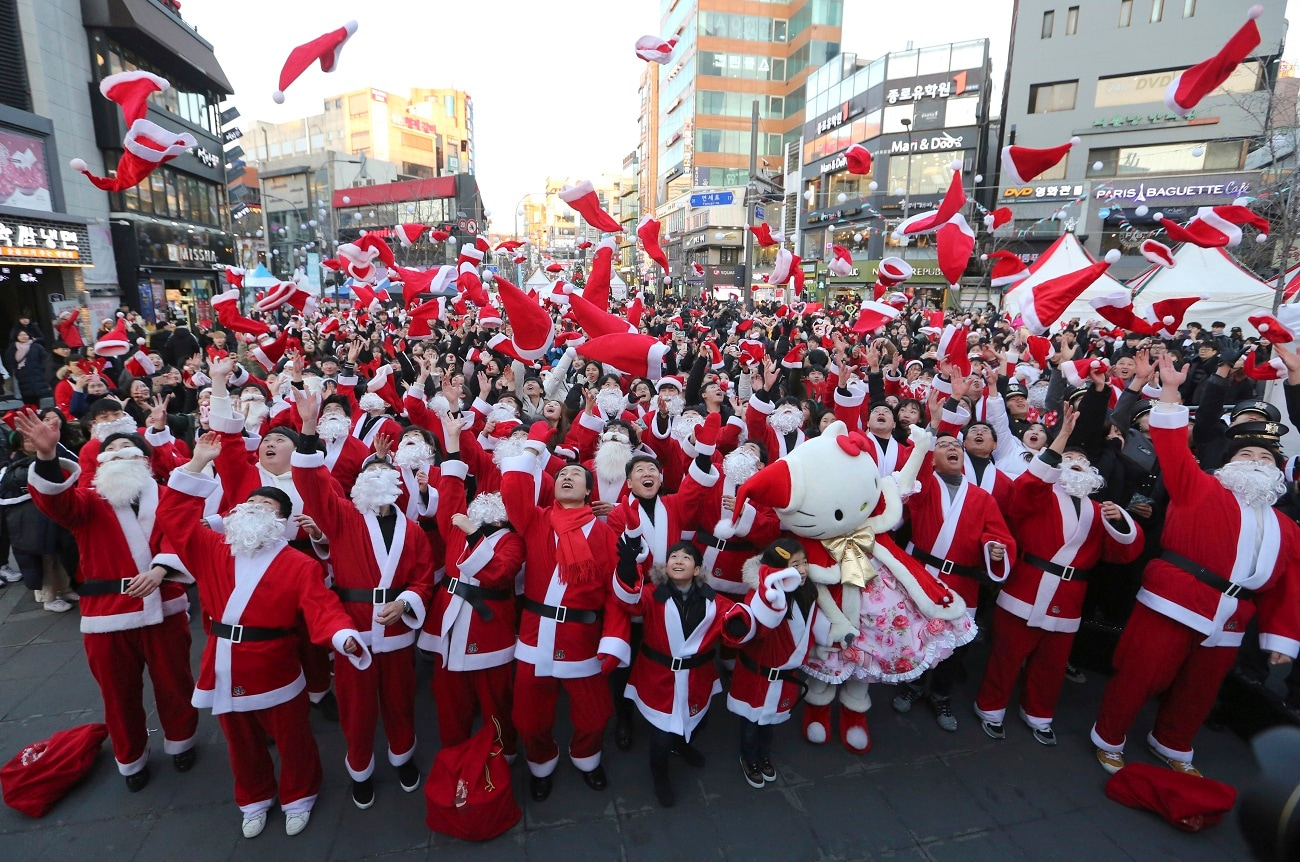 Volunteers clad in Santa Claus costumes throw their hats in the air as they gather to deliver gifts for the poor in downtown Seoul, South Korea. (AP Photo/Ahn Young-joon, File)