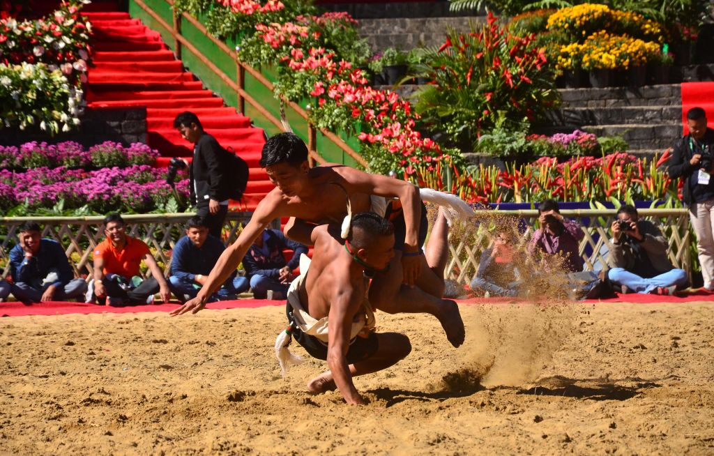 Naga tribesmen from Chakheshang tribe perform an art of wrestling during the Hornbill Festival at the Naga Heritage Village Kisama, some 12 Kms away from Kohima, the capital city of Nagaland. The annual Hornbill Festival which is celebrated from December 1-10 celebrates the cultural heritages of the Nagas. (Photo by Caisii Mao/NurPhoto via Getty Images)