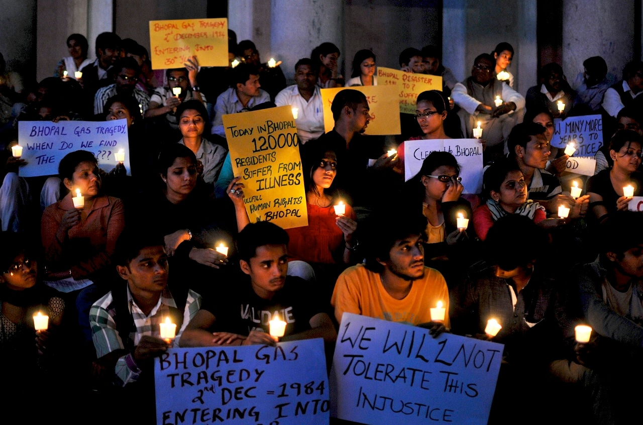 Activists from Bengaluru Solidarity Group, a social group, hold candles and placards during a vigil to commemorate the 30th anniversary of Bhopal gas tragedy, in Bengaluru on December 2, 2014. REUTERS/Abhishek N. Chinnappa